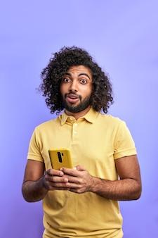 Красивый арабский мужчина использует смартфон, болтает с другом, набирает сообщение