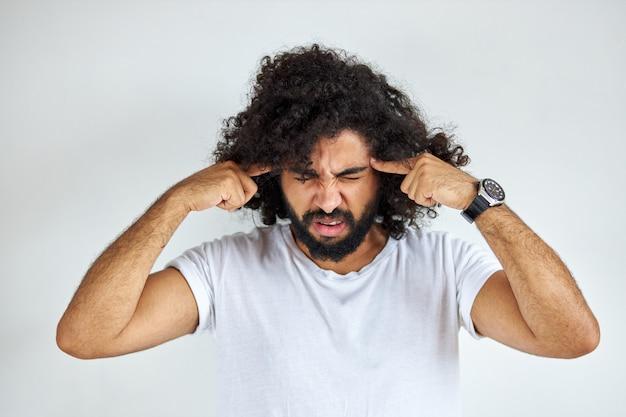 수염을 가진 잘 생긴 아라비아 사람은 고통 때문에 필사적으로 두통을 앓고 있습니다.