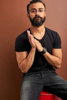 Handsome arabic male posing at camera while sitting on barrel in studio