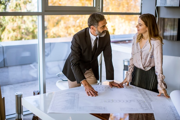 Handsome architect and his young female colleague checking plans and blueprints