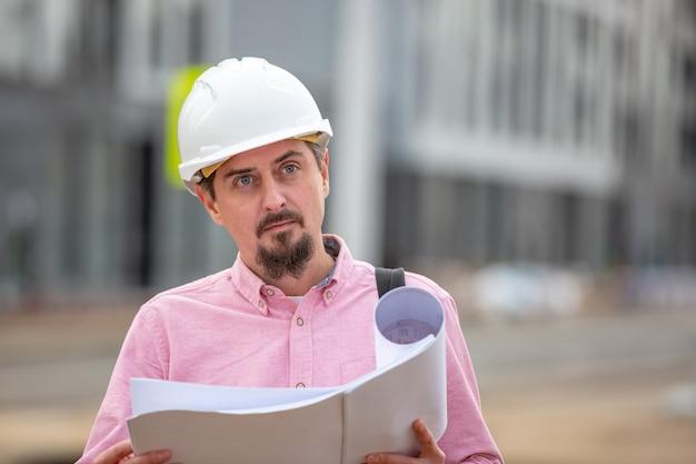 彼の手で青写真を保持している建築現場で屋外に立っているハンサムな建築家または監督者