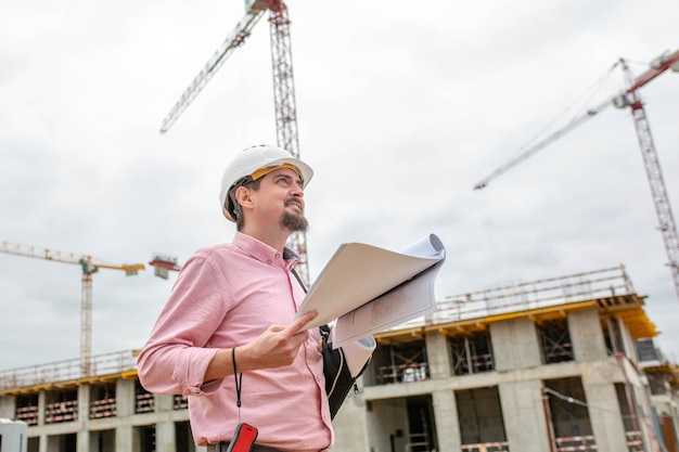 Handsome architect or supervisor standing outdoors on a building site holding a blueprint in his hands