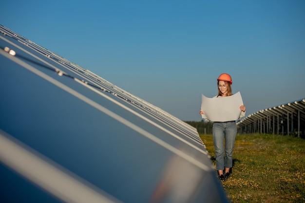 Красивая женщина-архитектор, изучающая проект карты или план проекта чертежа, деятельность работника, смотрящую на ферму фотоэлектрических элементов или поле солнечных панелей.