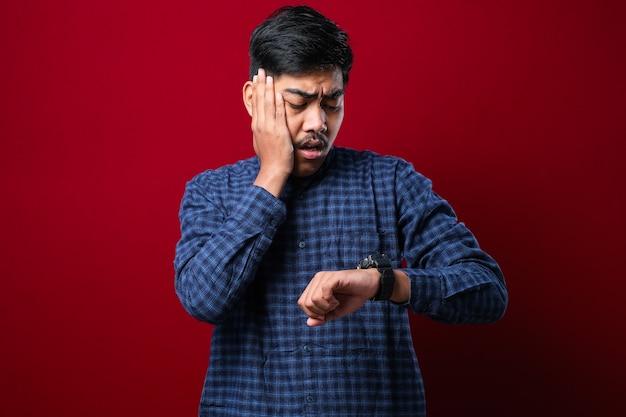 ハンサムなアジア人は、赤い背景に遅れるのを恐れて、心配している時計の時間を見てカジュアルな服を着ています