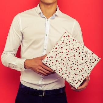 赤い背景の上にギフトボックスを保持しているハンサムなアジアのビジネスマン