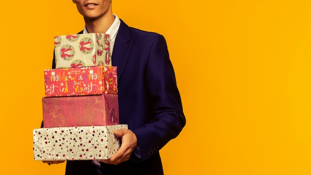 黄色の背景の上のギフトボックスを保持しているハンサムなアジアのビジネスマン