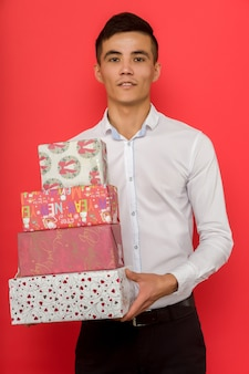 Handsome asian businessman holding gift box over red background