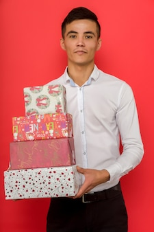 Handsome asian businessman holding gift box over red space