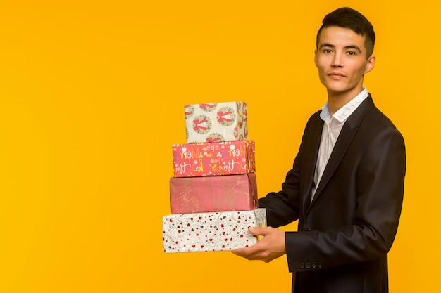 Handsome asian businessman holding gift box over yellow background