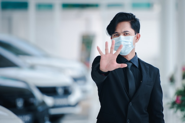 A handsome asian businessman is in a car sales office and he is sick and he wears a mask while working on business concepts.- colona virus