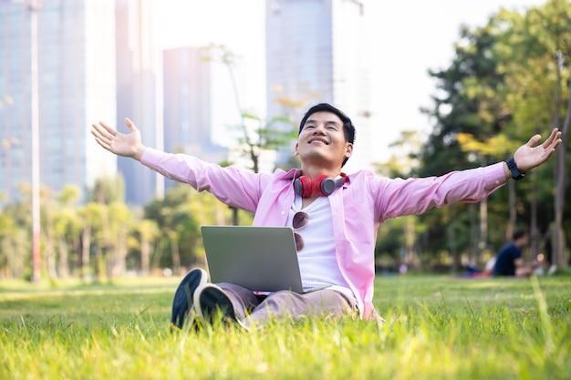 Красивый азиатский бизнесмен расслабляется и общается со своим ноутбуком на зеленой траве в центральном парке