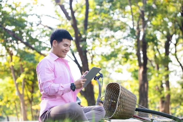 Красивый азиатский бизнесмен расслабляется и использует планшет для видеосвязи со своим другом на зеленой траве в центральном парке