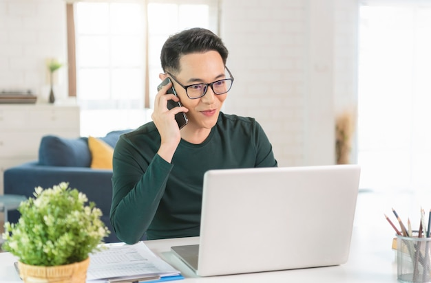 ノートパソコンでテーブルに座って、ホームオフィスでスマートフォンで話しているハンサムなアジアのビジネスマン。