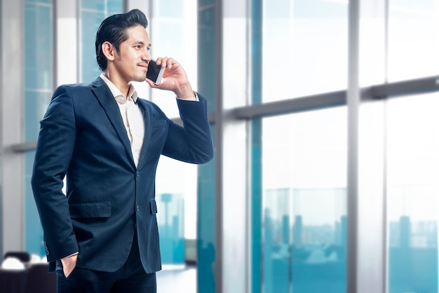 Handsome asian businessman standing while talking on the cellphone