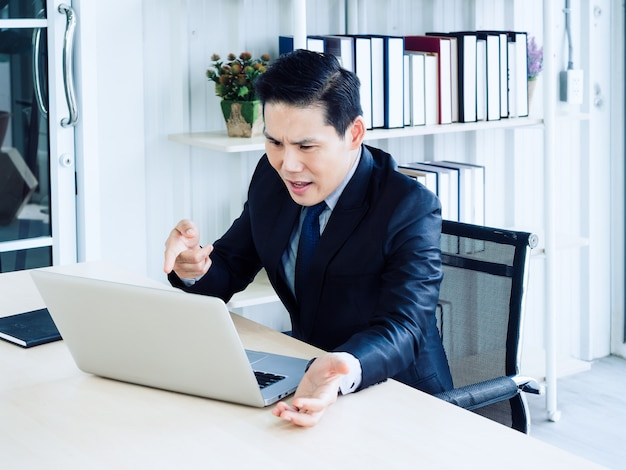 Handsome asian businessman in suit video call, complaining to colleague through laptop computer in meeting online working, video conference