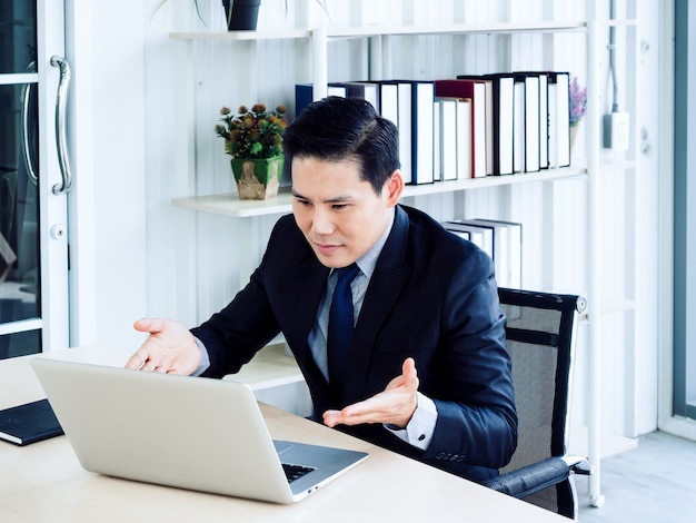 Handsome asian businessman in suit video call, explaining to colleague through laptop computer in meeting online working, video conference