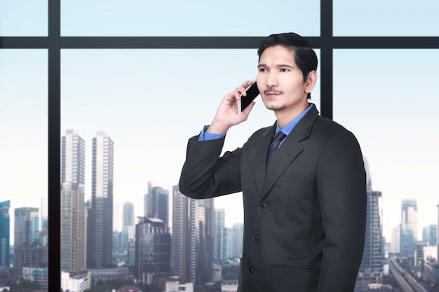 Handsome asian businessman talking on the cellphone