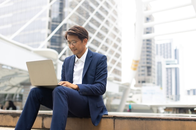 Handsome asian businessman working outdoors with computer