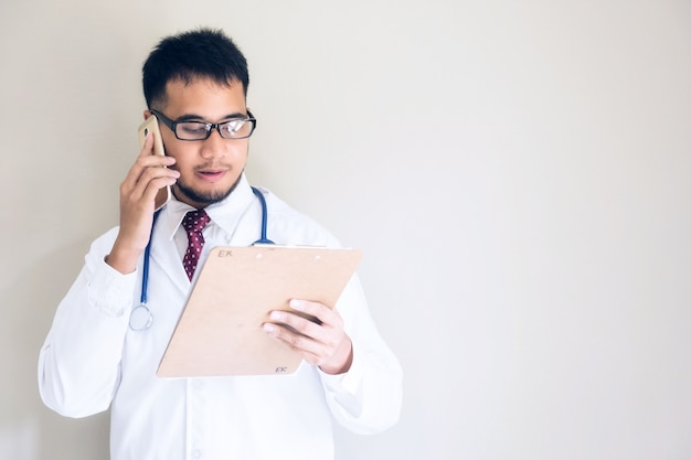 Handsome asian doctor at emergency room (er) talking with patient relative by smartphone