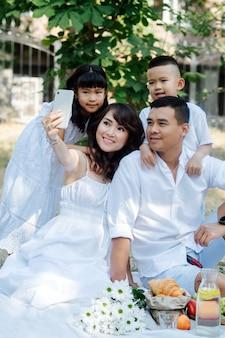 公園で自分撮りをしている白い服を着たハンサムなアジアの家族。彼らはピクニックをしていて、初秋の最後の暖かい日を楽しんでいます。木の影にいる親とその子供たち。