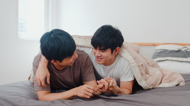Handsome asian gay couple talking on bed at home. young asian lgbtq+ guy happy relax rest together spend romantic time after wake up in bedroom at modern house in the morning .