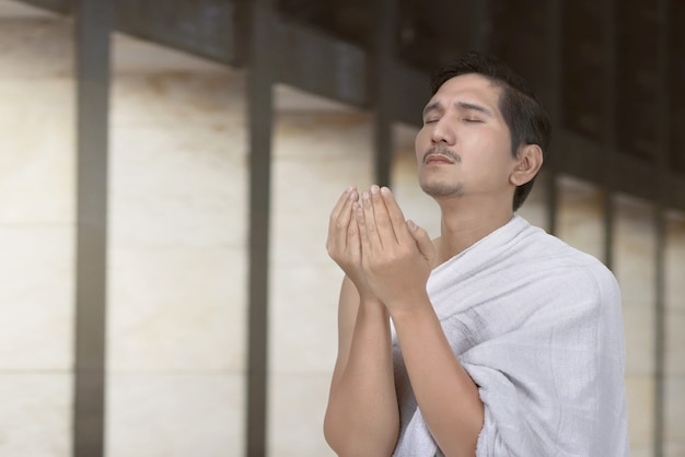 Handsome asian hajj pilgrim praying