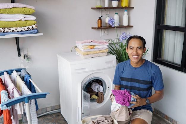 Красивый азиатский домохозяйка кладет грязную одежду одну за другой в стиральную машину и стирает дома