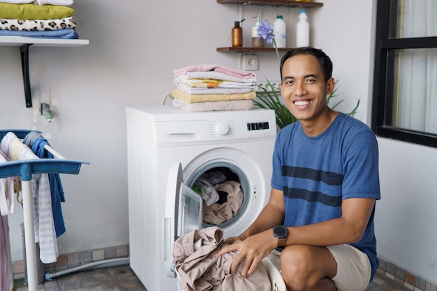 Handsome asian househusband putting dirty clothes one by one into washing machine and doing laundry at home