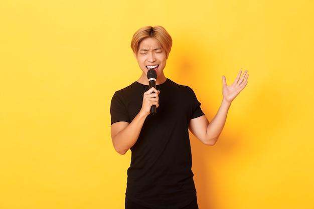 Красивый азиатский певец, корейский парень со страстью поет песню в караоке в микрофон, стоя у желтой стены