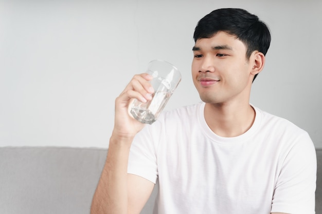 Красивый азиатский мужчина пьет стакан воды на диване в гостиной