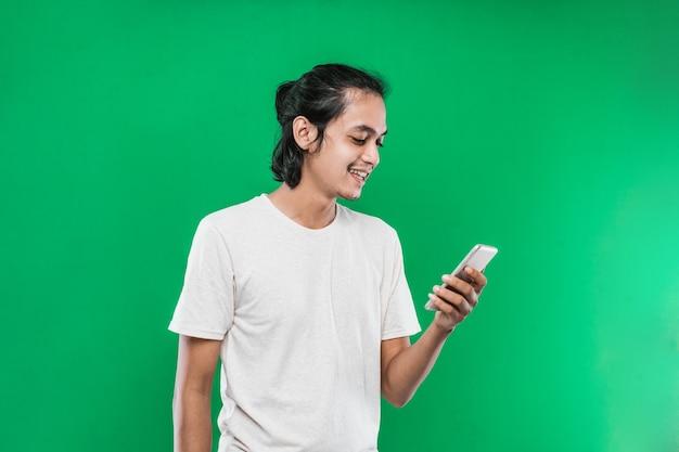 緑の背景に分離された幸せな笑顔の表情で携帯電話を保持し、見てハンサムなアジア人男性