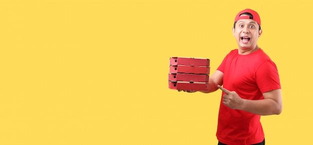 黄色の壁に分離された段ボール箱に食品注文イタリアンピザを与える赤い帽子でハンサムなアジア男