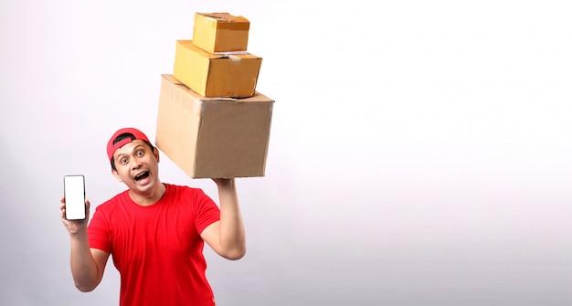 空白の白い空の画面で携帯電話を保持している分離された段ボール箱に小包郵便ボックスで立っている赤い帽子でハンサムなアジア人。