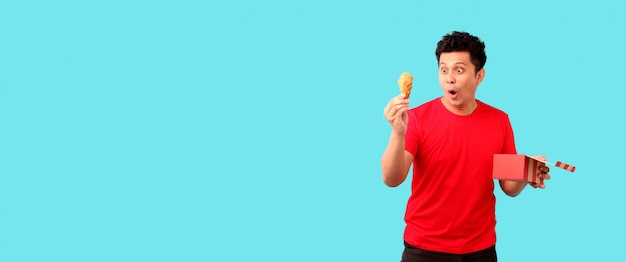 Handsome asian man is eating fried chicken deliciously