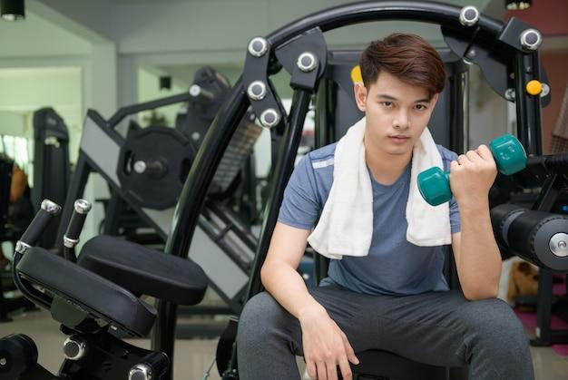 Handsome asian man lifting dumbbells