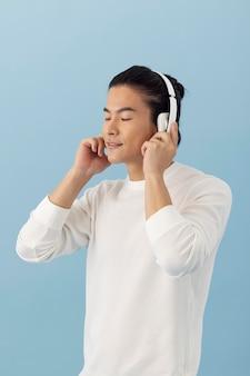Uomo asiatico bello che ascolta la musica tramite le cuffie