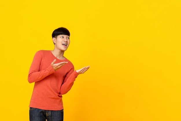 Handsome asian man looking up to empty space aside with hands open