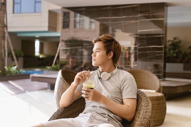 晴れた夏の日にリラックスして座っているハンサムなアジア人男性。
