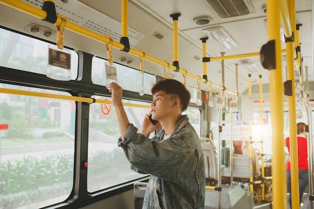 市バスに立って携帯電話で話しているハンサムなアジア人男性