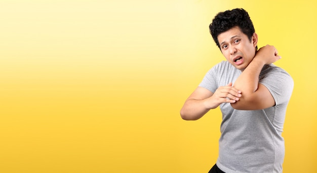 Handsome asian man touching elbow with painful facial expression.on yellow wall.