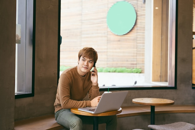 Handsome asian man using laptop sitting on wooden table in coffee shop with a cup of coffee