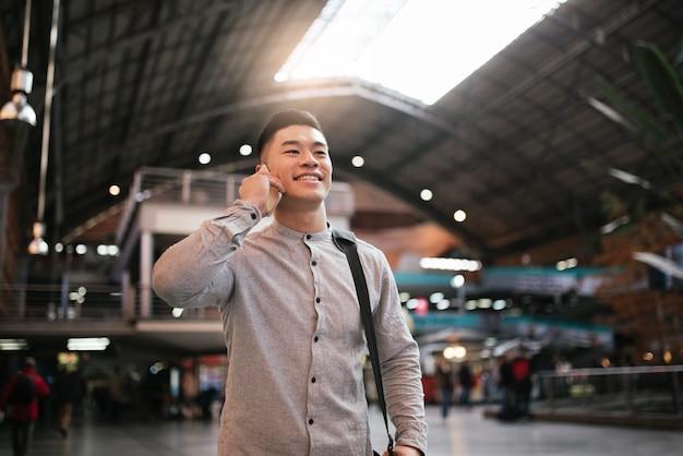 기차역에서 모바일을 사용하는 잘생긴 아시아 남자. 통신 개념입니다.