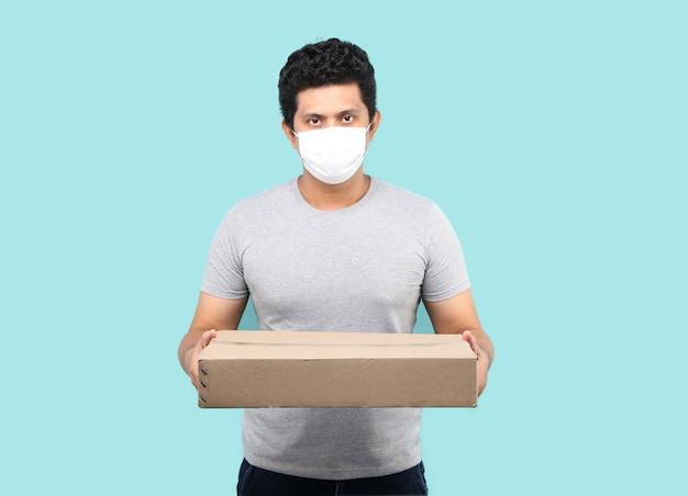 Маска красивого азиатского человека нося для того чтобы защитить от зародыша и вируса. холдинг с посылки почтовый ящик в картонных коробках на голубом фоне в студии.