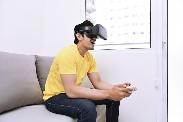 Handsome asian man wearing virtual reality while playing video games