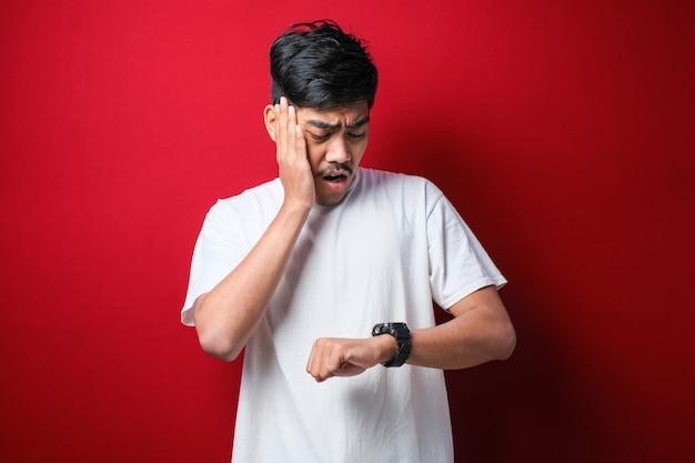 赤い背景に遅れるのを恐れて、心配している時計の時間を見て白いtシャツを着ているハンサムなアジア人男性