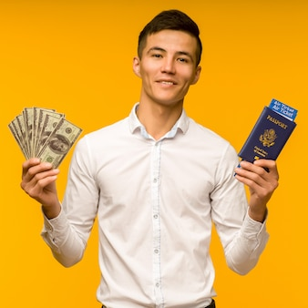 A handsome asian man in a white shirt rejoices in winning the lottery. he is holding a passport with air tickets and money dollars on a yellow space.
