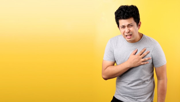 Handsome asian man with heart pain,on yellow wall.