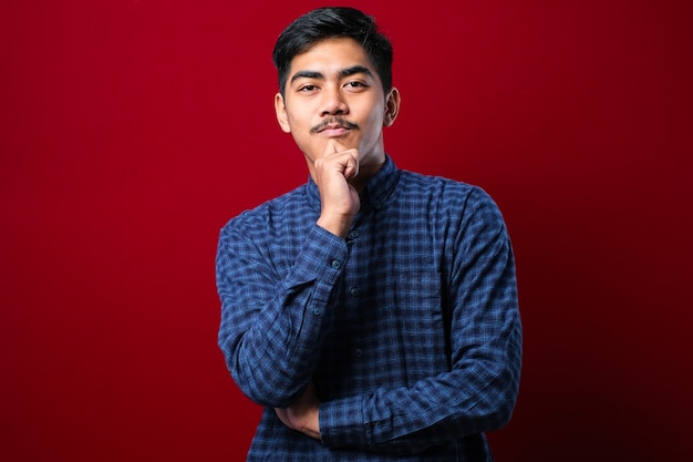 Handsome asian man with mustache wearing casual shirt over red background looking confident at the camera with smile with crossed arms and hand raised on chin. thinking positive.