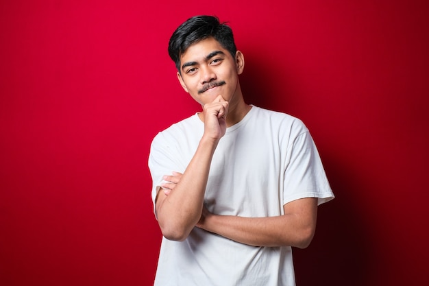 Handsome asian man with mustache wearing white tshirt over red background looking confident at the camera with smile with crossed arms and hand raised on chin. thinking positive.
