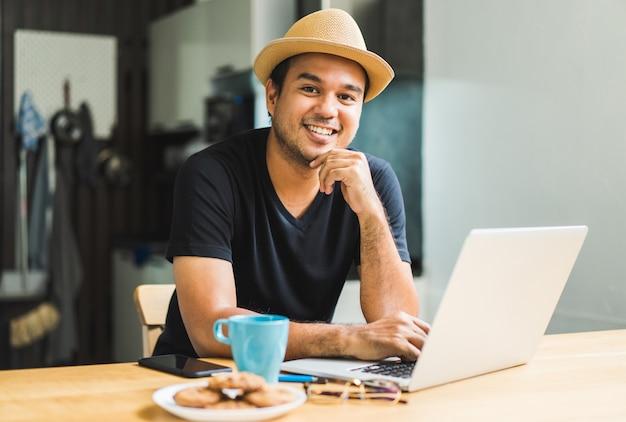 Красивый азиатский мужчина, работающий дома с ноутбуком